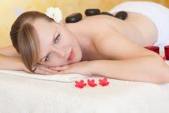 Mujer joven hermosa que consigue masaje de piedra caliente fotografía de archivo