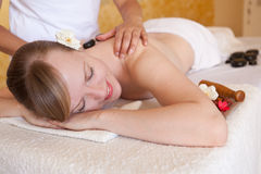 Mujer joven hermosa que consigue masaje de piedra caliente imágenes de archivo libres de regalías
