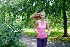 Mujer joven hermosa que corre en parque verde en día de verano soleado Fotos de archivo libres de regalías