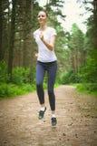 Mujer joven hermosa que corre en parque verde en día de verano soleado Fotografía de archivo
