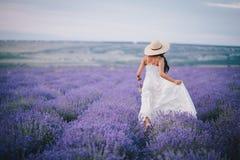 Mujer joven hermosa que corre en un campo de la lavanda Imagen de archivo libre de regalías