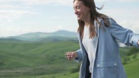 Mujer joven hermosa que corre a través de un campo verde almacen de metraje de vídeo