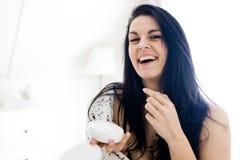 Mujer joven hermosa que cuida sobre su piel con la loción hidratante - gran humor fotografía de archivo libre de regalías