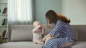 Mujer joven hermosa que disfruta de la maternidad, jugando con el bebé activo, felicidad almacen de video