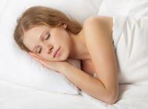 Mujer joven hermosa que duerme en cama Fotos de archivo