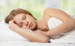 Mujer joven hermosa que duerme en cama Fotos de archivo libres de regalías