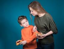 Mujer joven hermosa que elige entre los cereales y los pasteles. Pérdida de peso. Imagenes de archivo