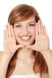 Mujer joven hermosa que enmarca su cara Imagen de archivo libre de regalías