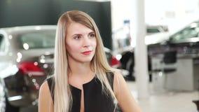 Mujer joven hermosa que escucha la condición de la sala de exposición en la compra metrajes