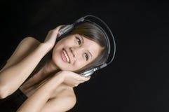 Mujer joven hermosa que escucha la música Imagen de archivo libre de regalías