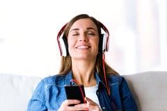Mujer joven hermosa que escucha la música con el teléfono móvil en casa Imagen de archivo