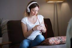Mujer joven hermosa que escucha la música con el teléfono móvil en casa Imagenes de archivo
