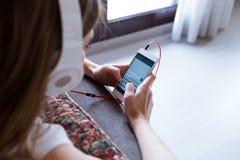 Mujer joven hermosa que escucha la música con el teléfono móvil en casa Imágenes de archivo libres de regalías