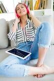 Mujer joven hermosa que escucha la música con la tableta digital Imagen de archivo