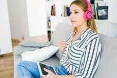 Mujer joven hermosa que escucha la música con la tableta digital Imágenes de archivo libres de regalías