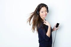 Mujer joven hermosa que escucha la música con los auriculares Imágenes de archivo libres de regalías