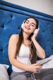 Mujer joven hermosa que escucha la música en auriculares en cama en casa Foto de archivo