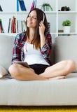 Mujer joven hermosa que escucha la música en casa Fotos de archivo libres de regalías