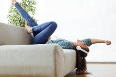 Mujer joven hermosa que escucha la música en casa Imagen de archivo libre de regalías