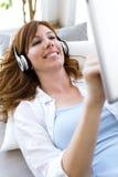 Mujer joven hermosa que escucha la música en casa Imágenes de archivo libres de regalías