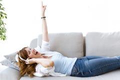 Mujer joven hermosa que escucha la música en casa Foto de archivo libre de regalías