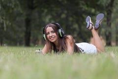 Mujer joven hermosa que escucha la música en naturaleza Foto de archivo libre de regalías
