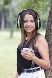 Mujer joven hermosa que escucha la música en naturaleza Imagen de archivo