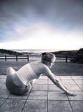 Mujer joven hermosa que estira en el mar Imagen de archivo