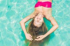 Mujer joven hermosa que flota en la opinión superior relajante de la piscina holida imagenes de archivo