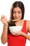 Mujer joven hermosa que goza del cereal de desayuno Imagen de archivo libre de regalías