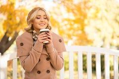Mujer joven hermosa que goza del olor del café en el parque en otoño imagen de archivo libre de regalías