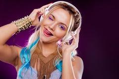 Mujer joven hermosa que guiña y que muestra la lengua Música y goce que escuchan imagen de archivo