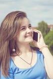 Mujer joven hermosa que habla en el teléfono celular al aire libre Imagen de archivo libre de regalías