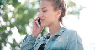 Mujer joven hermosa que habla en el teléfono durante día soleado Fotos de archivo