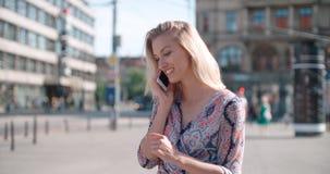 Mujer joven hermosa que habla en el teléfono durante día soleado Imagen de archivo libre de regalías