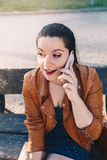 Mujer joven hermosa que habla en el teléfono elegante del teléfono elegante en un parque de la ciudad que se sienta en un banco imagenes de archivo