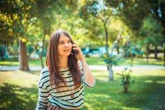 Mujer joven hermosa que habla en el teléfono en ciudad Imagen de archivo