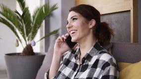 Mujer joven hermosa que habla en el teléfono móvil en casa Mujer relajada en el teléfono móvil que se sienta en el sofá El hablar almacen de metraje de vídeo