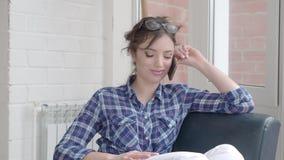 Mujer joven hermosa que habla en el teléfono móvil en casa Mujer relajada en el teléfono móvil que se sienta en el sofá Muchacha  almacen de video