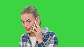 Mujer joven hermosa que habla en el teléfono móvil seriamente en una pantalla verde, llave de la croma metrajes