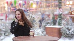 Mujer joven hermosa que habla en el teléfono y el té caliente de consumición durante la feria de la Navidad almacen de video