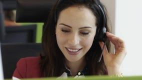 Mujer joven hermosa que habla en las auriculares en centro de llamada de oficina metrajes