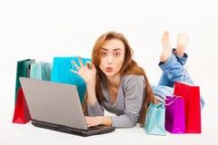Mujer joven hermosa que hace compras sobre Internet Imagen de archivo libre de regalías