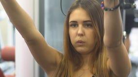 Mujer joven hermosa que hace ejercicios para consolidar el simulador del hombro almacen de metraje de vídeo