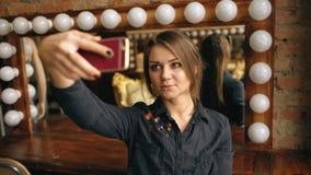 Mujer joven hermosa que hace el retrato del selfie en un smartphone en vestuario dentro Imágenes de archivo libres de regalías