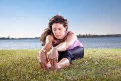 Mujer joven hermosa que hace estirando ejercicio en hierba verde. Imagenes de archivo