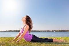 Mujer joven hermosa que hace estirando ejercicio en hierba verde. Imagen de archivo