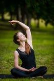 Mujer joven hermosa que hace estirando ejercicio en hierba verde en el parque Entrenamiento de la yoga Imagen de archivo libre de regalías