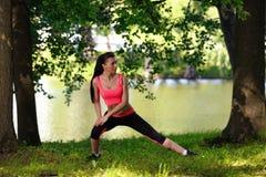 Mujer joven hermosa que hace estirando ejercicio en parque cerca del río Foto de archivo libre de regalías