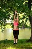Mujer joven hermosa que hace estirando ejercicio en parque cerca del río Fotos de archivo libres de regalías